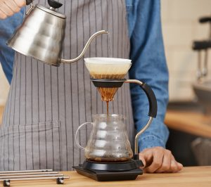 someone pouring a pour over with a gooseneck kettle